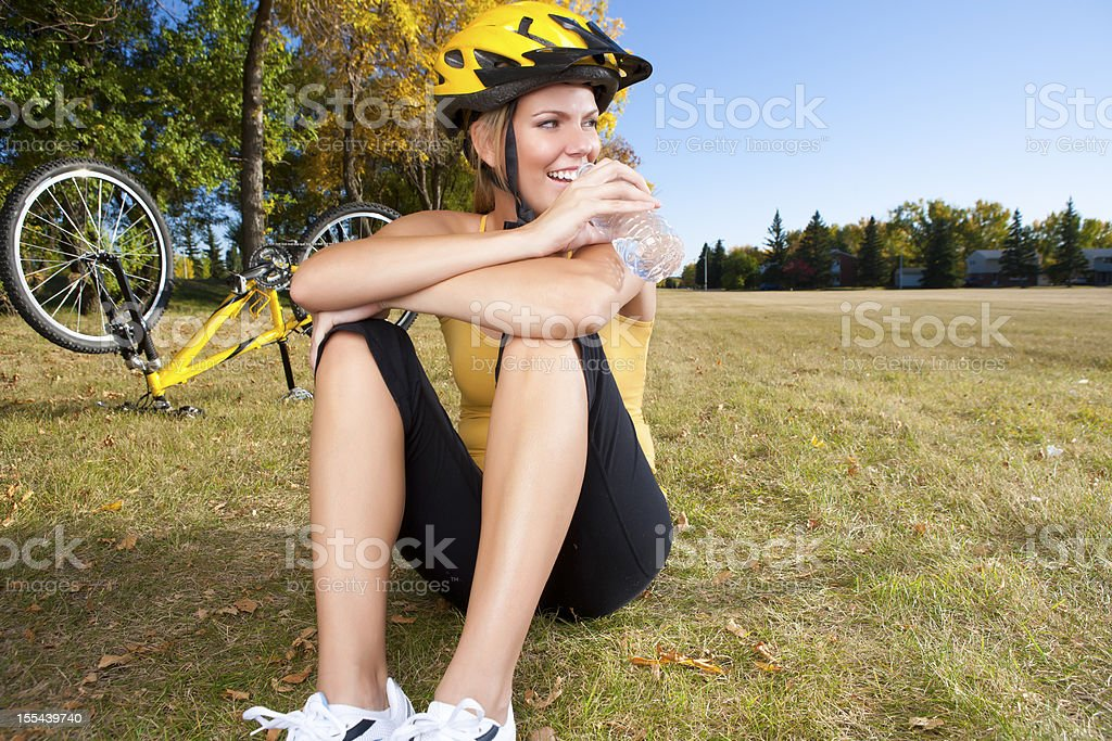 Smiling female biker drinking water royalty-free stock photo