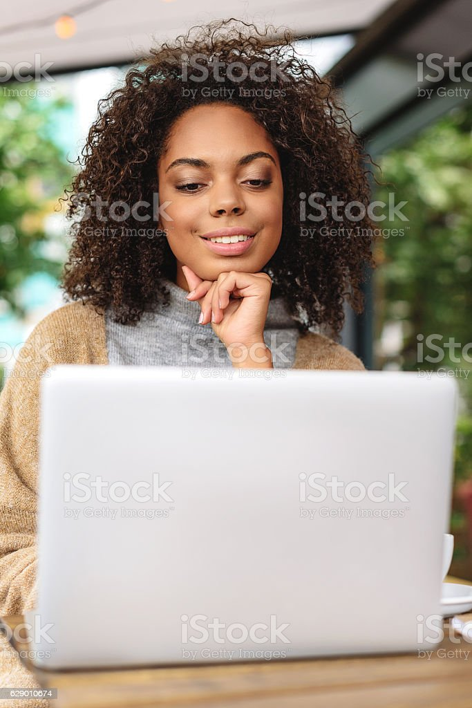smiling female blogger sitting in front of the laptop stock photo
