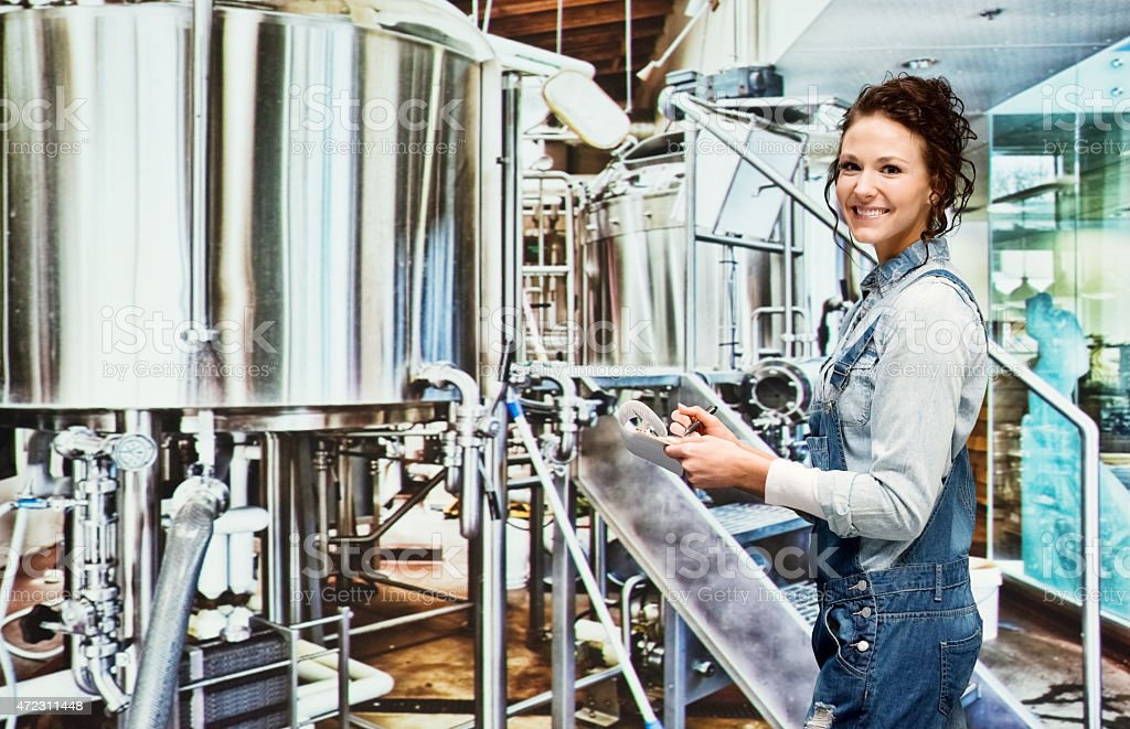 Smiling female brewmaster working in industry stock photo