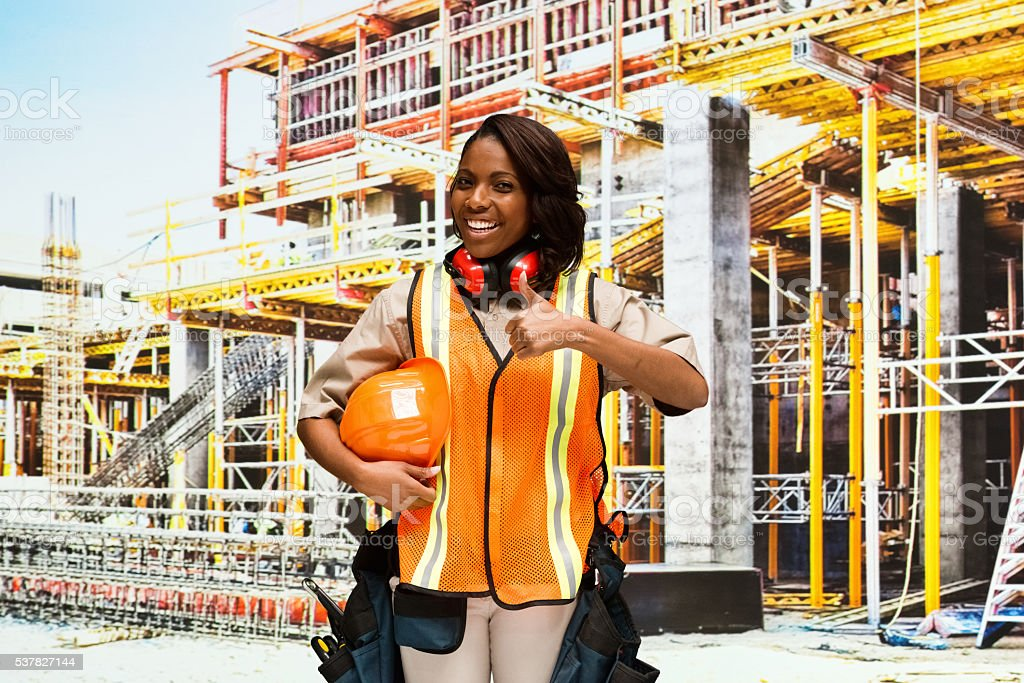 Smiling female building contractor giving thumbs...