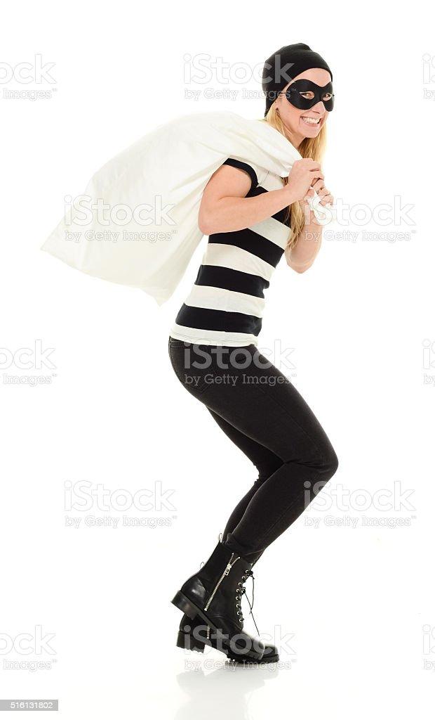 Smiling female burglar carrying money bag stock photo