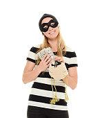 Smiling female burglar holding money