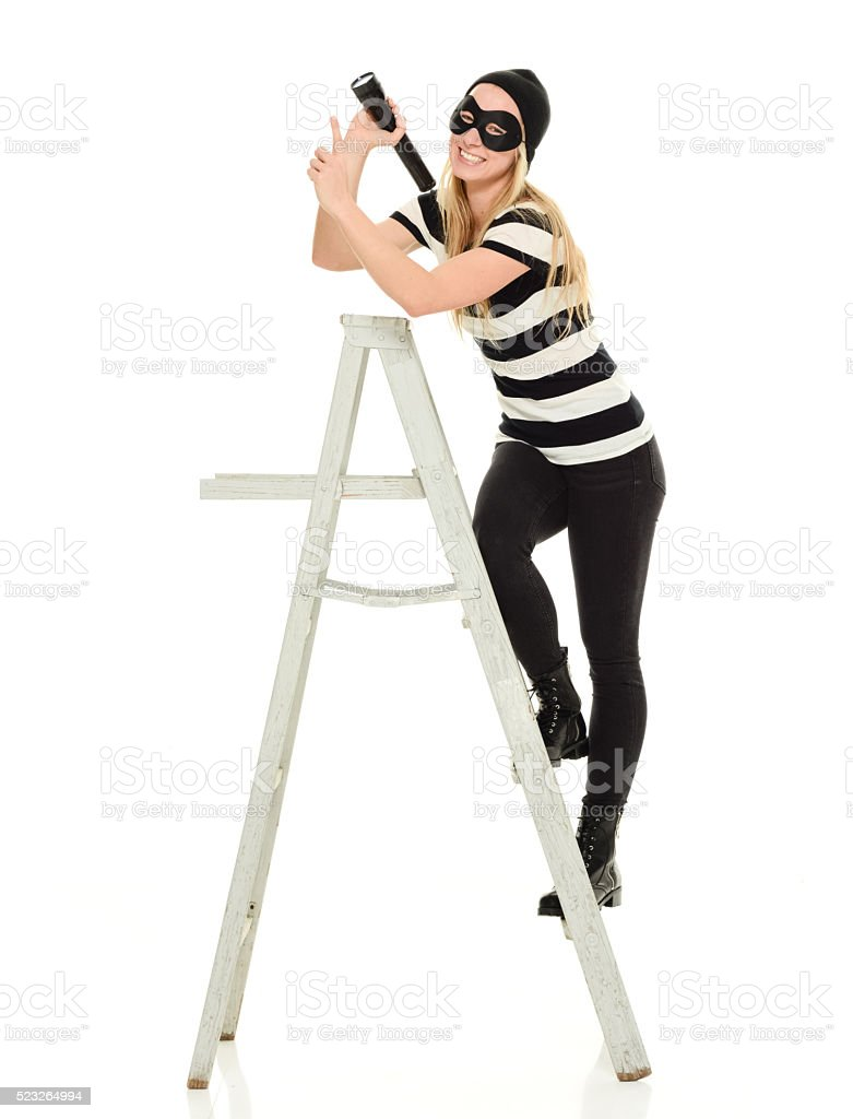 Smiling female burglar on ladder and pointing away stock photo