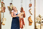 Smiling female butcher on phone in shop