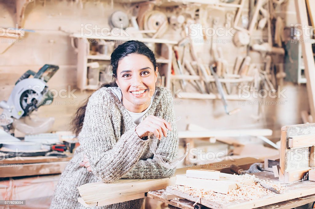 Smiling female carpenter at workshop stock photo