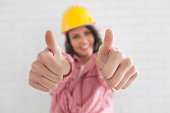 Smiling female construction worker making thumbs up gesture