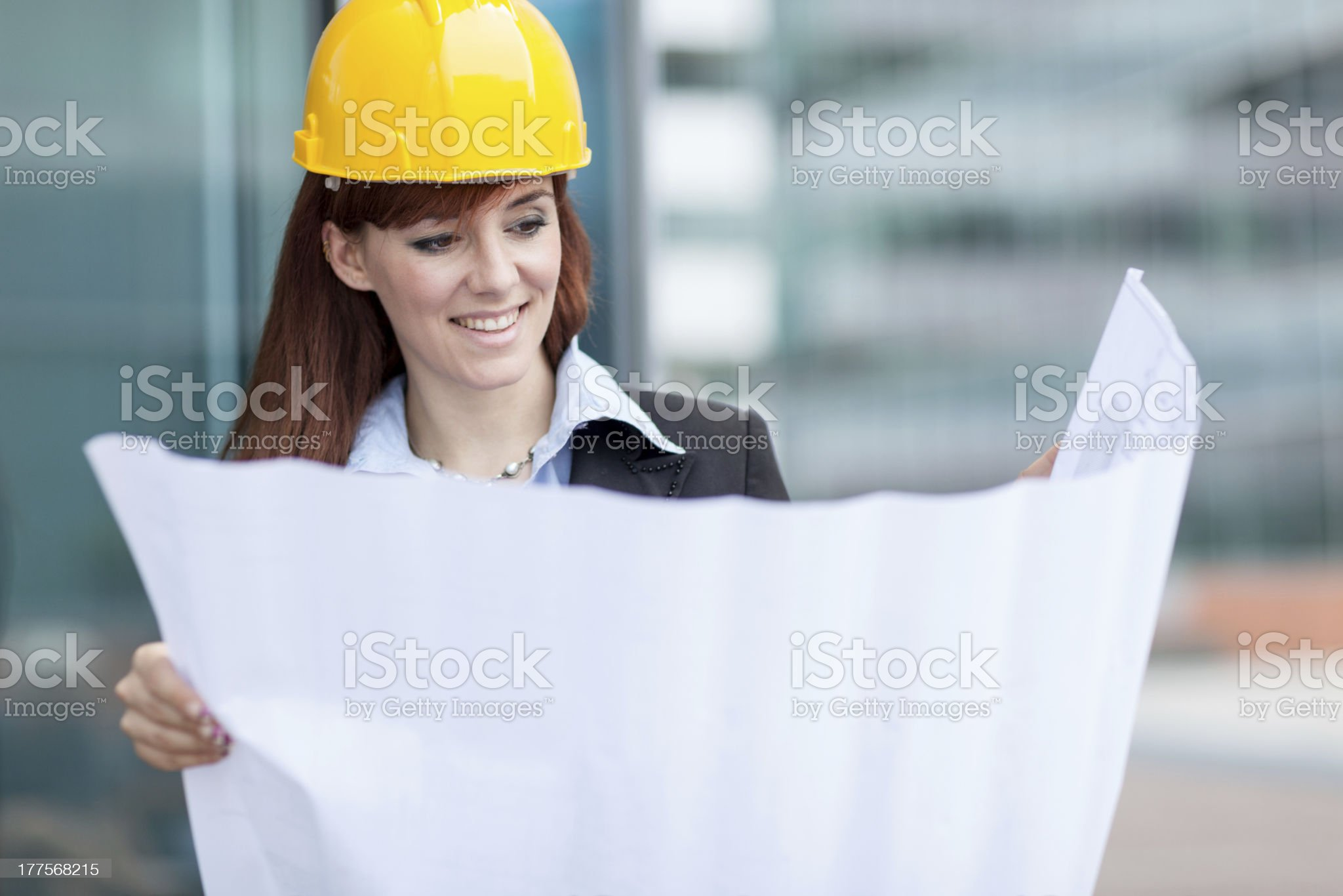 Smiling female constructor with blueprints royalty-free stock photo