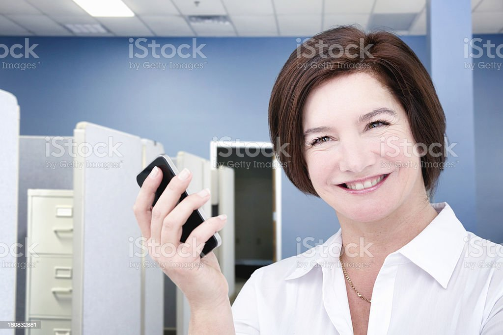 Smiling female cubicle worker with smart phone royalty-free stock photo