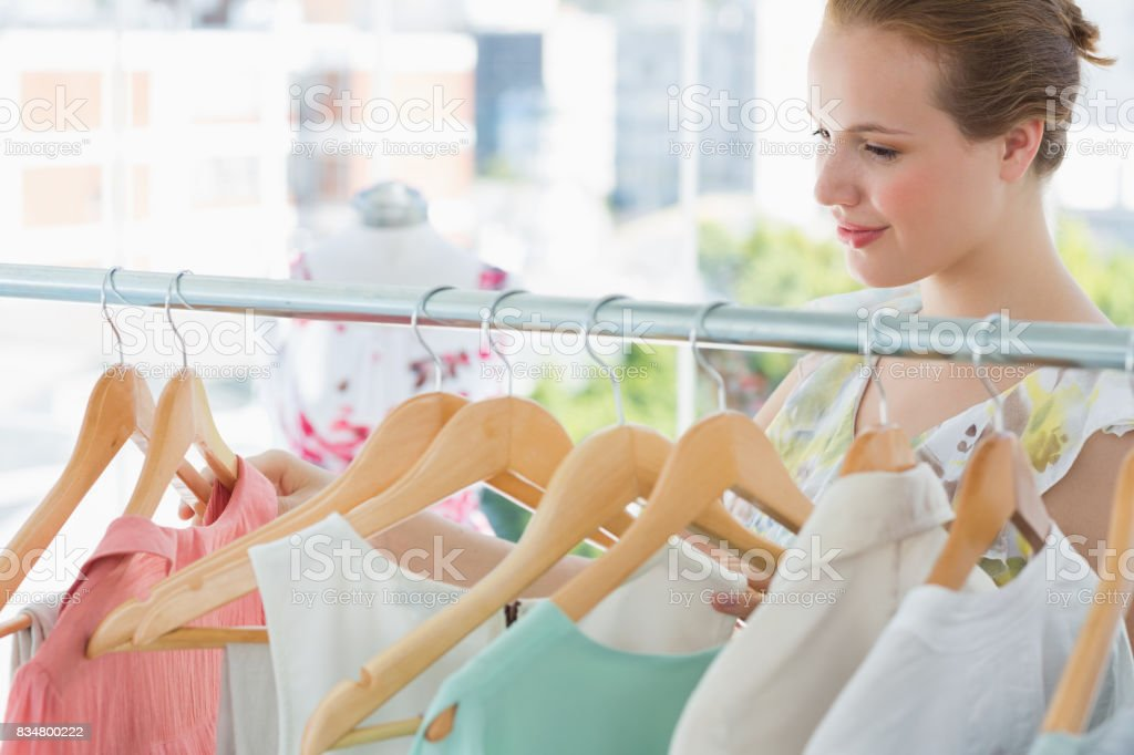 Smiling female customer at clothing rack in store stock photo