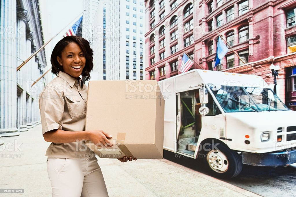 Smiling female delivery person holding box outdoors stock photo