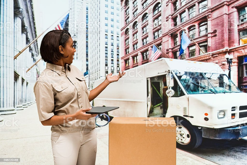 Smiling female delivery person presenting stock photo