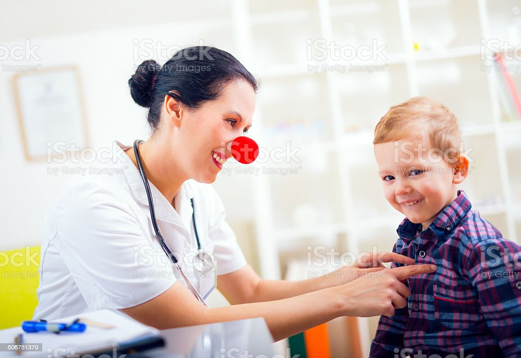 Smiling female doctor clown and little boy patient stock photo