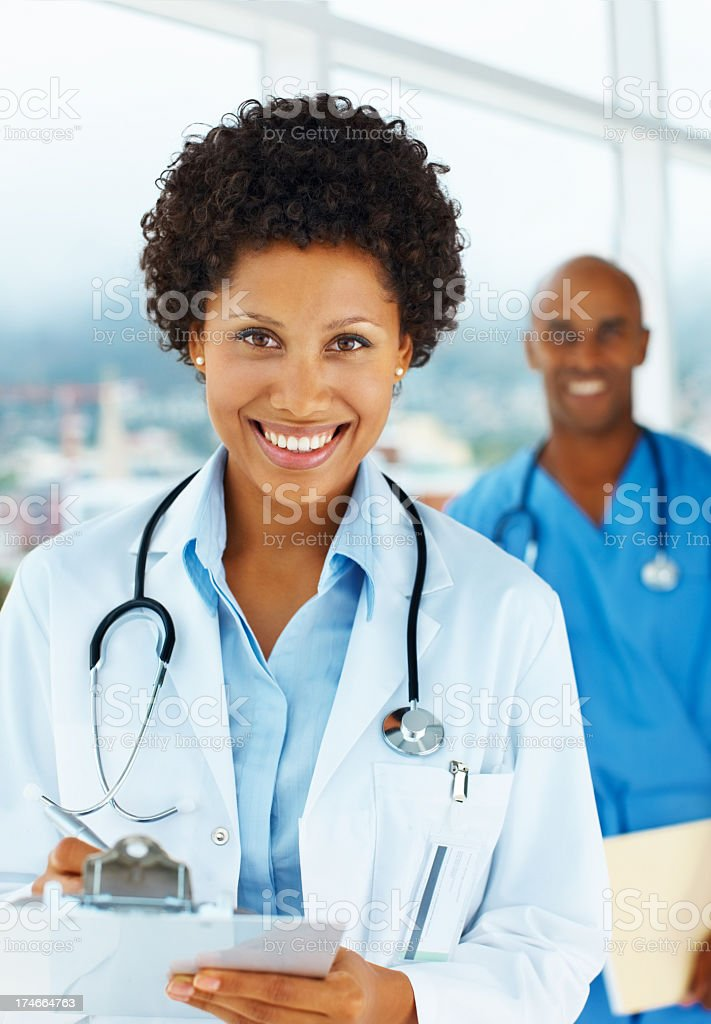Smiling female doctor with male colleague in background royalty-free stock photo