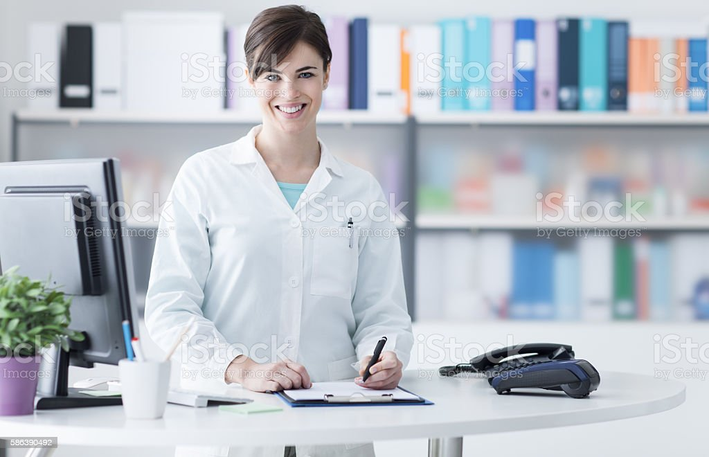 Smiling female doctor working at the clinic stock photo