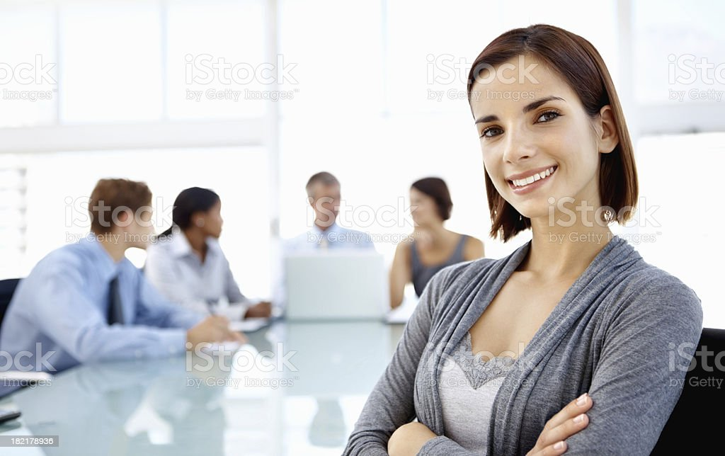 Smiling, female executive with group working in background royalty-free stock photo