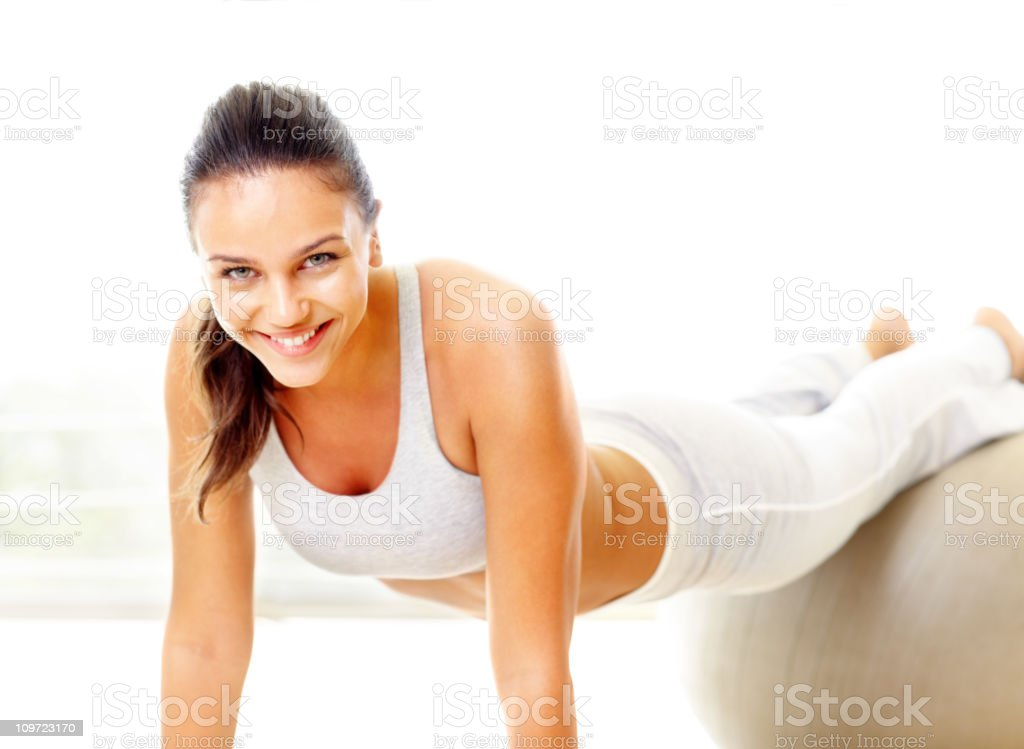 Smiling female exercising on a fitness ball royalty-free stock photo