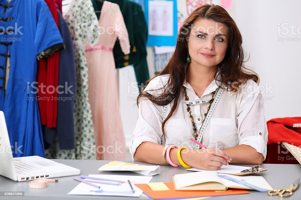 Smiling female fashion designer holding drawing pad and pencil m stock photo