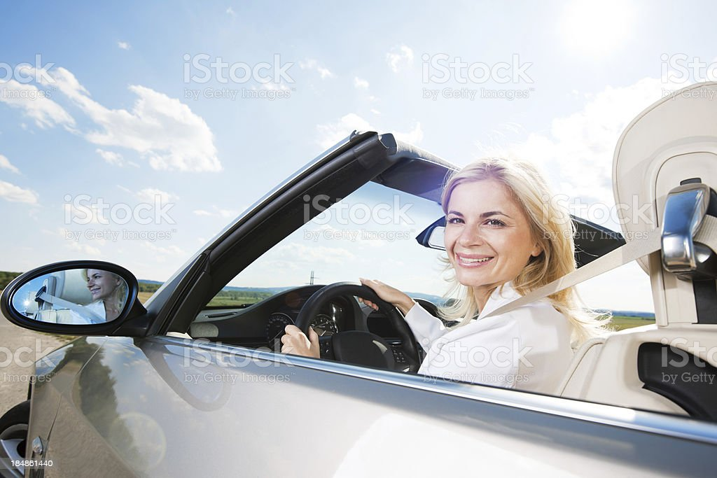 Smiling female fastening driving a Convertible car. royalty-free stock photo