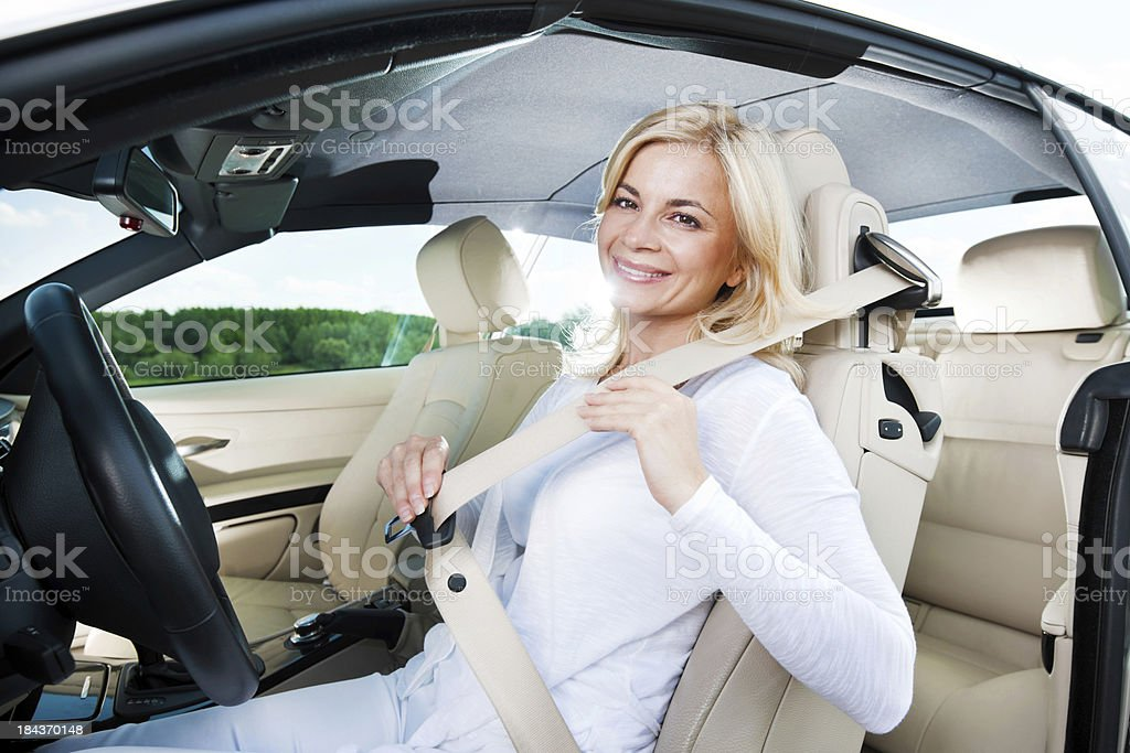 Smiling female fastening her seat belt. stock photo