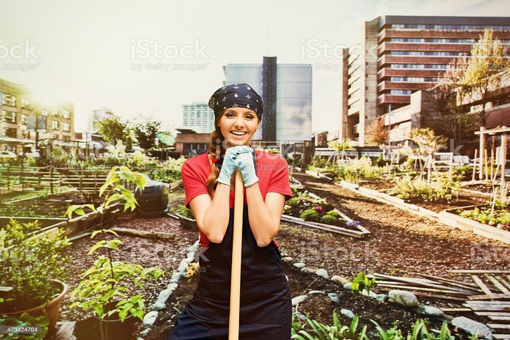 Smiling female gardener holding shovel in garden stock photo