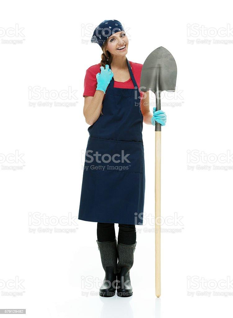 Smiling female gardener holding shovel stock photo