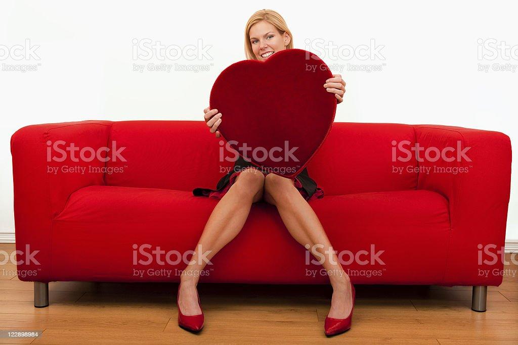 Smiling female holding a big heart shape stock photo
