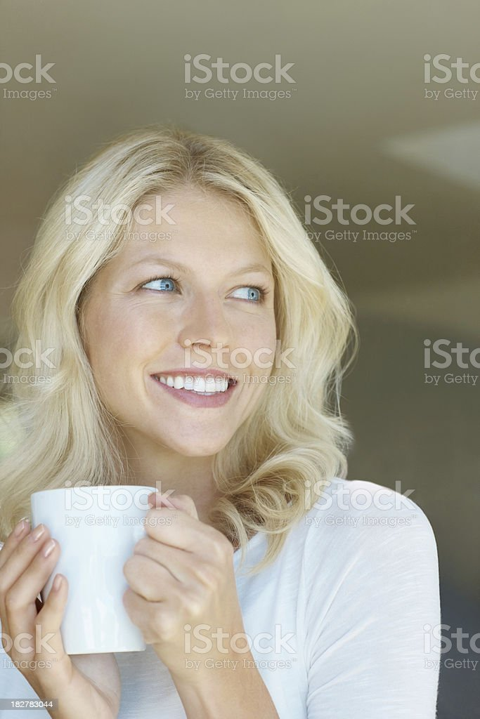 Smiling female holding a coffee cup and looking away royalty-free stock photo