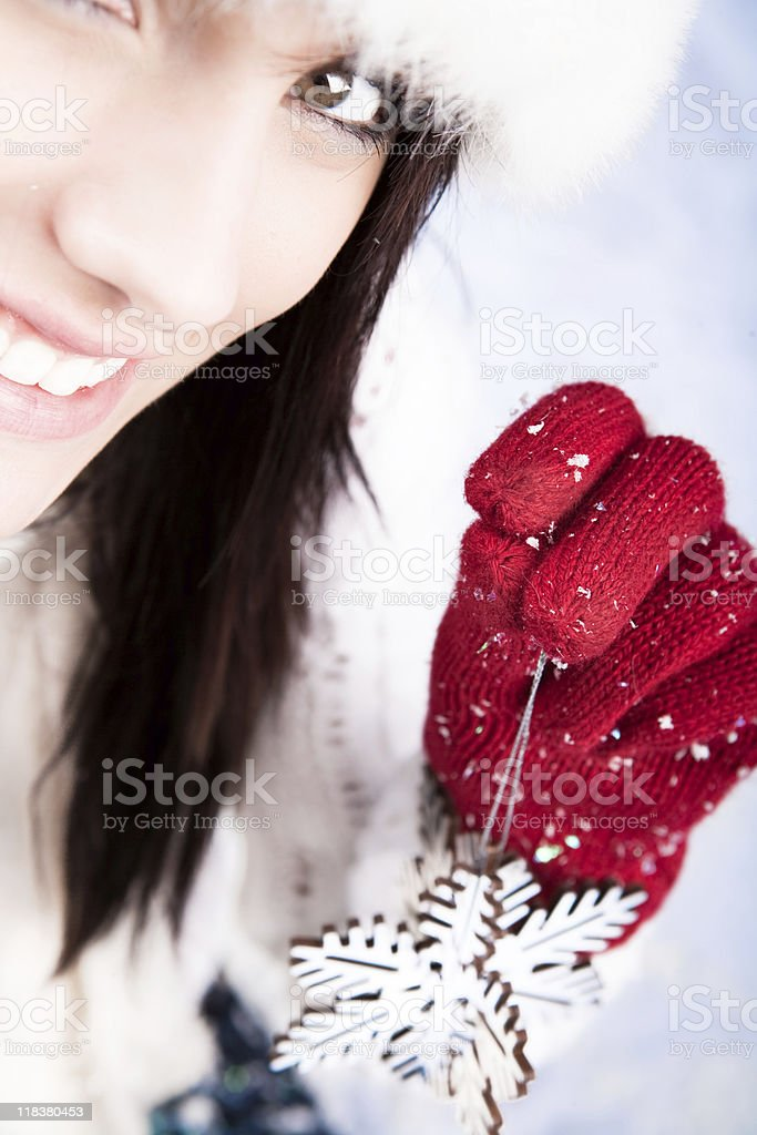 Smiling female holding a snowflake ornament royalty-free stock photo