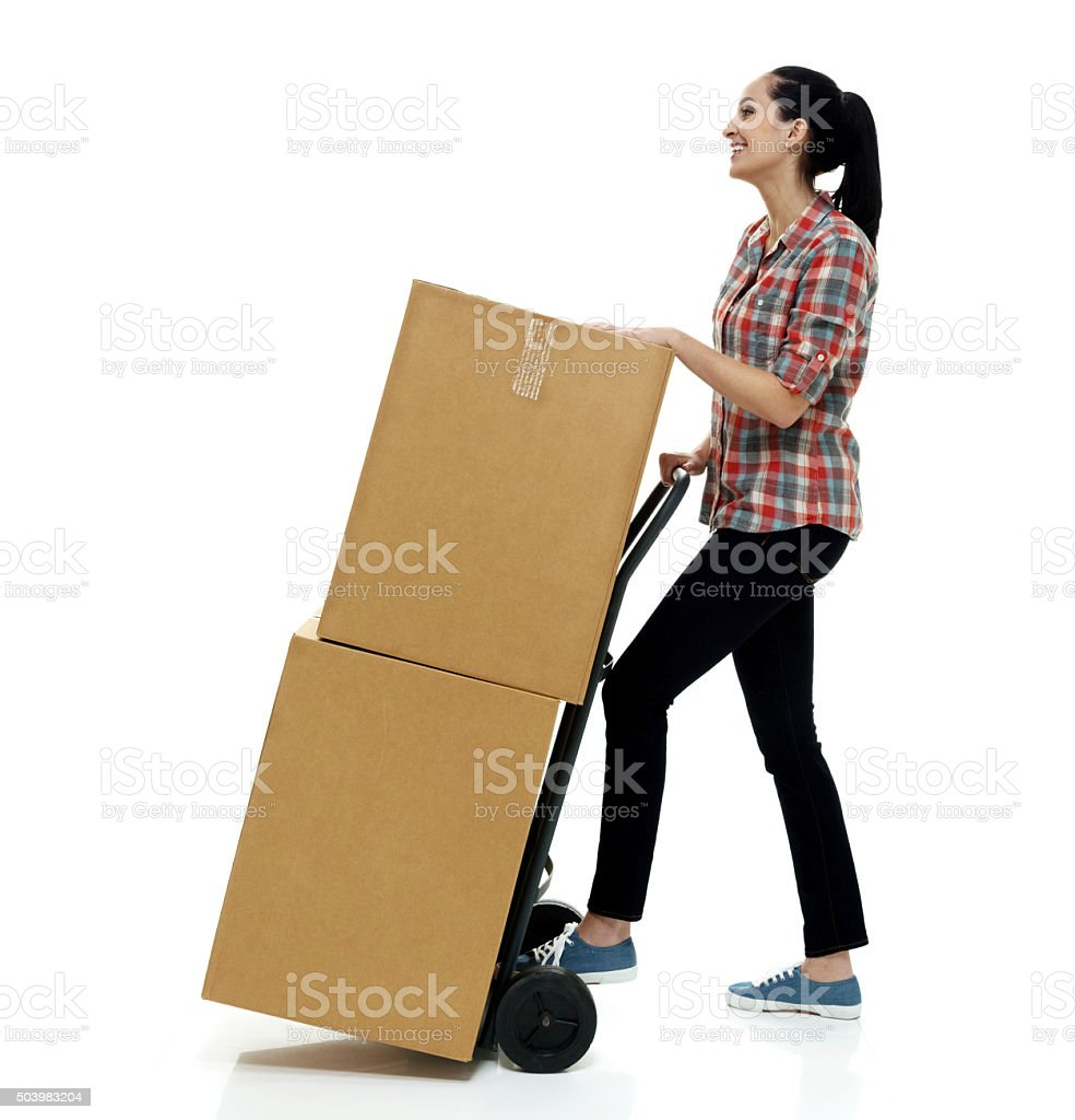 Smiling female holding hand truck stock photo