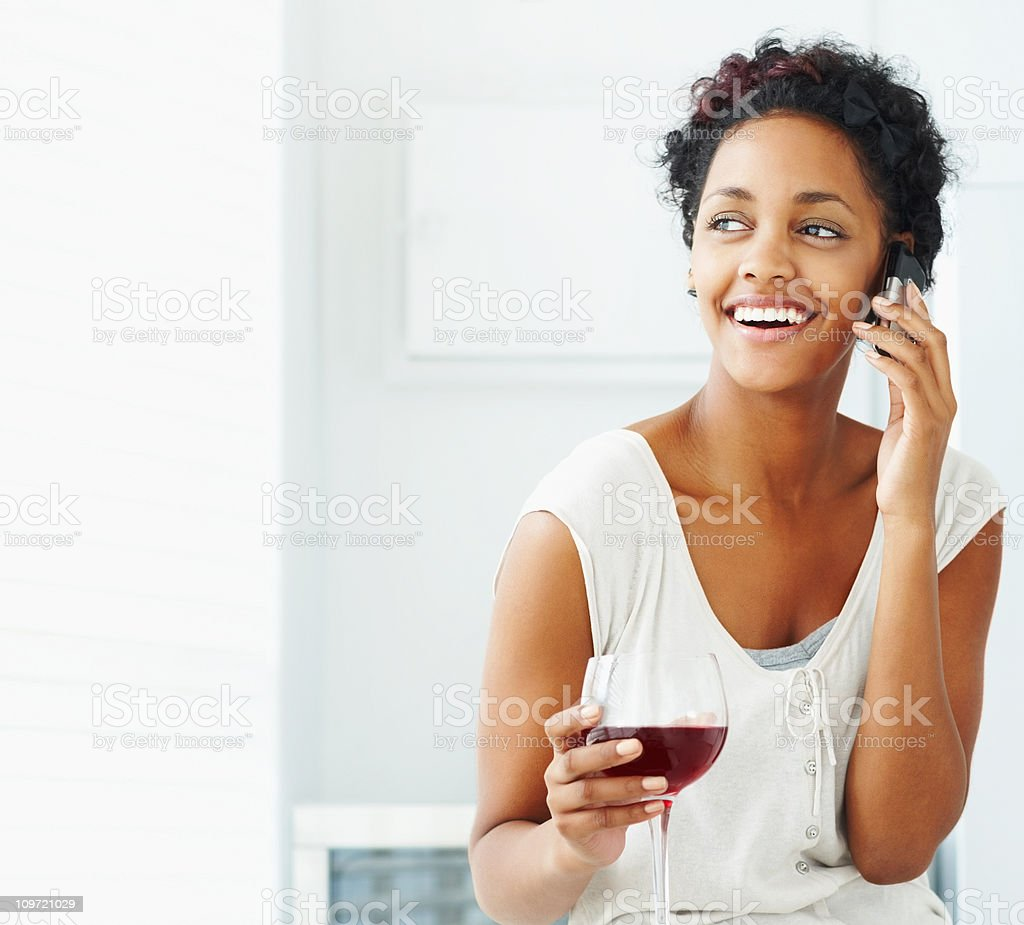 Smiling female holding wineglass while talking on cellphone royalty-free stock photo