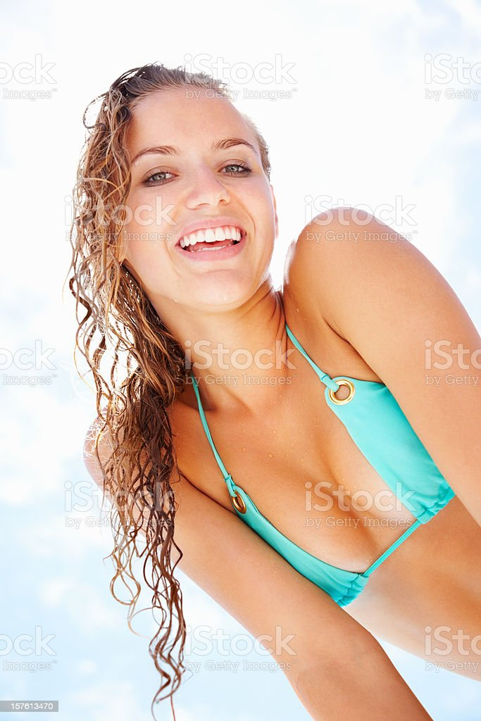 Smiling female in blue bikini against a cloudy sky royalty-free stock photo