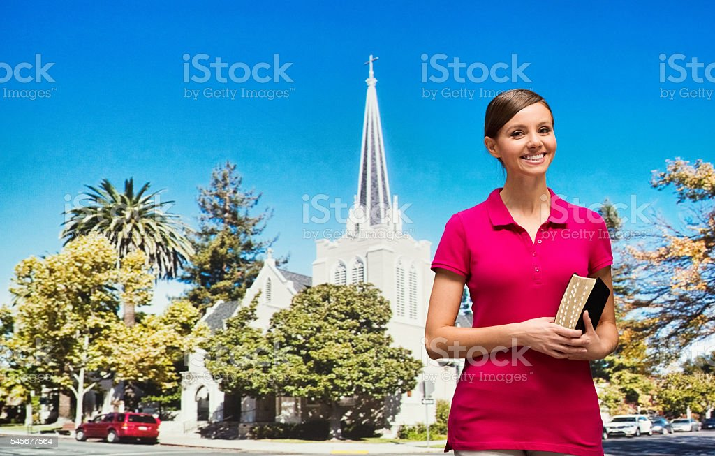 Smiling female in front of church stock photo