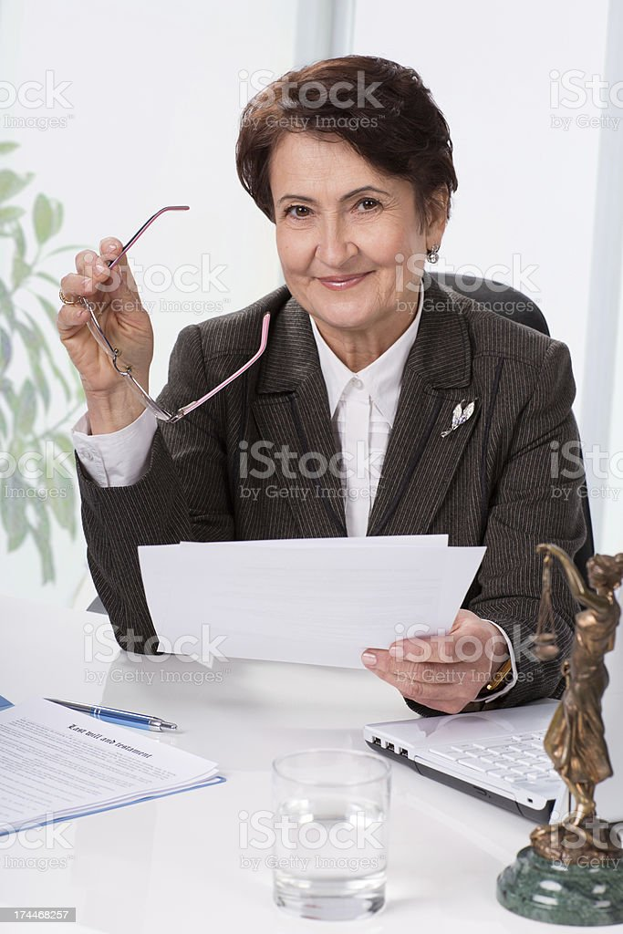 Smiling female lawyer holding glasses and papers at a desk royalty-free stock photo