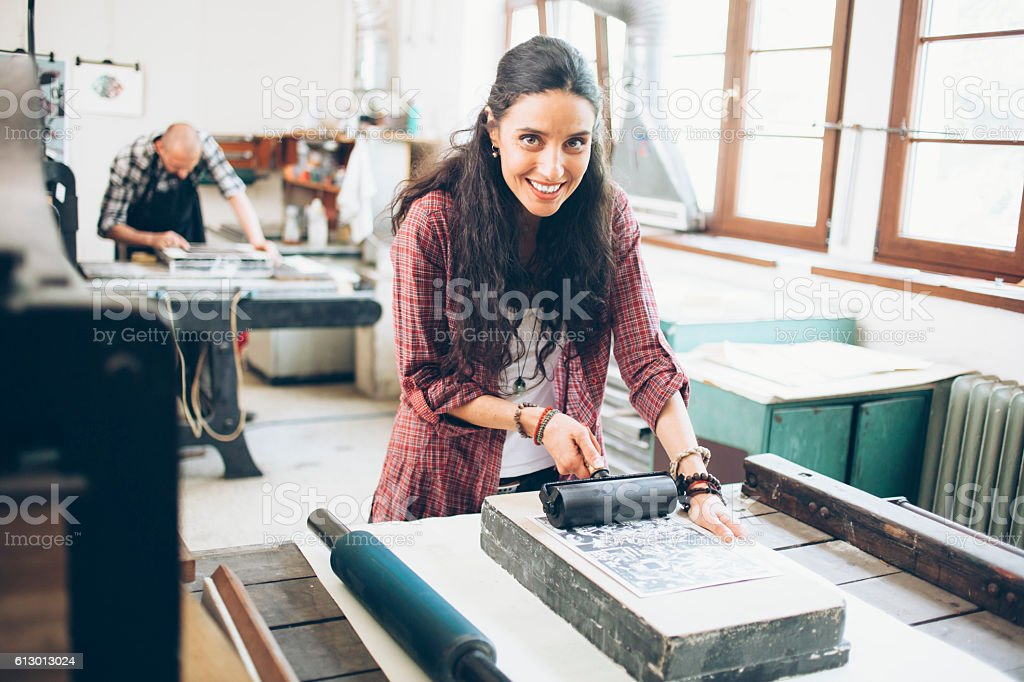 Smiling female lithograph worker using roller at printing house stock photo