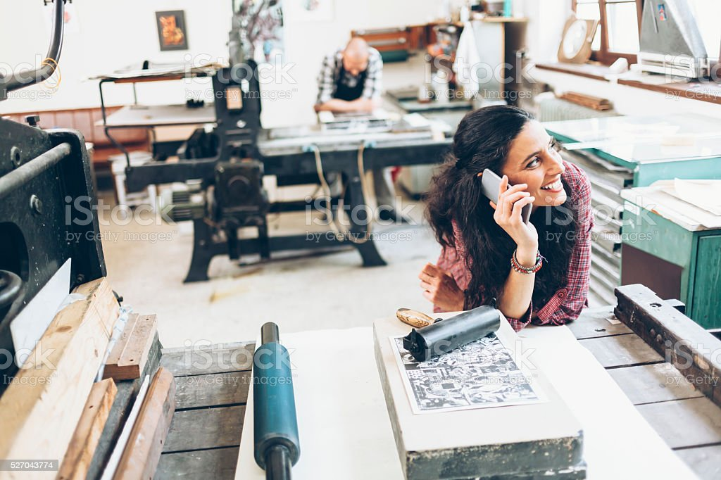 Smiling female lithography worker using phone at printing house stock photo