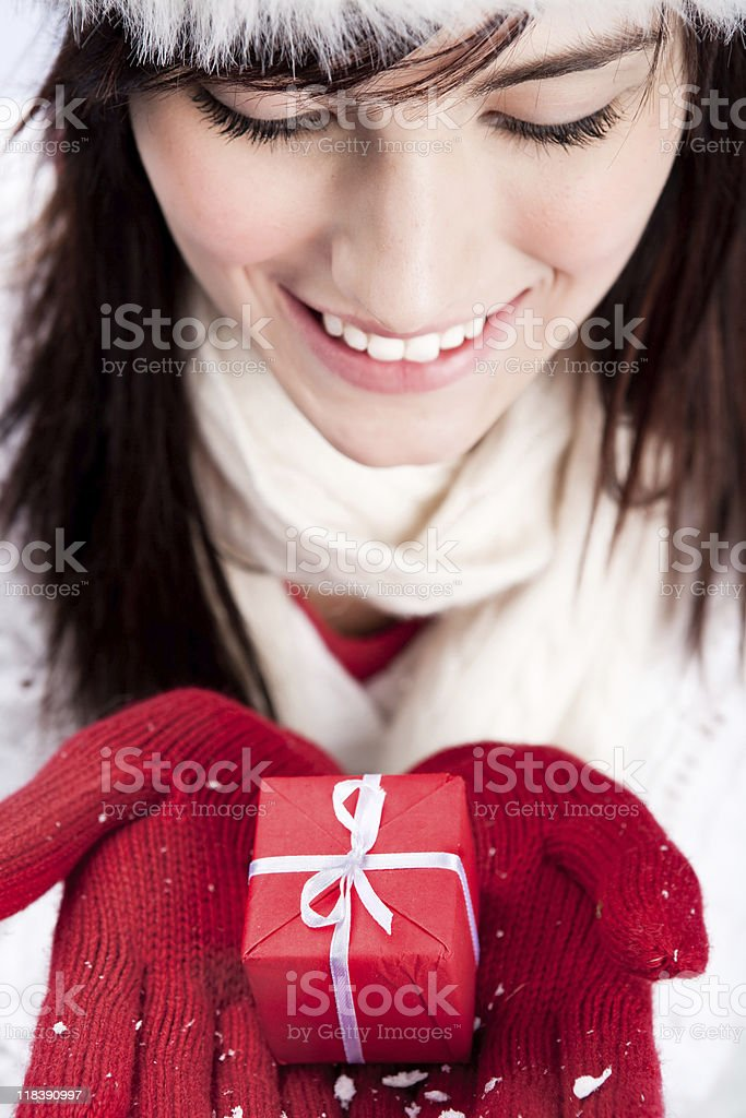 Smiling female looking down at her red christmas present royalty-free stock photo