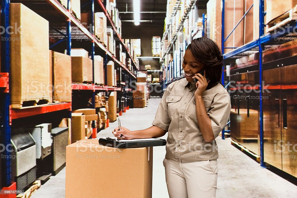 Smiling female manager on phone in warehouse stock photo
