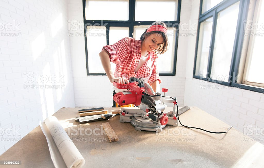 Smiling female manual worker using a circular saw stock photo