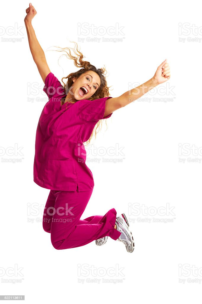 Smiling Female Nurse Throwing Apple Over White Background stock photo