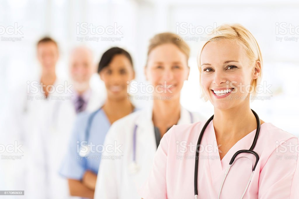 Smiling Female Nurse With Medical Team stock photo