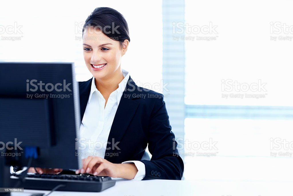 Smiling female office worker working on a computer royalty-free stock photo