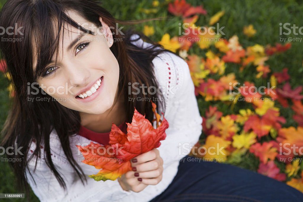 Smiling female playing with autumn leaves royalty-free stock photo