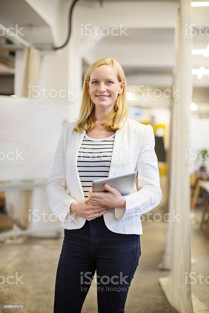 Smiling female professional holding tablet computer stock photo
