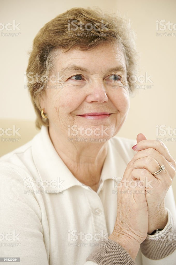 Smiling Female Senior Citizen with Hands Clasped in Joy royalty-free stock photo