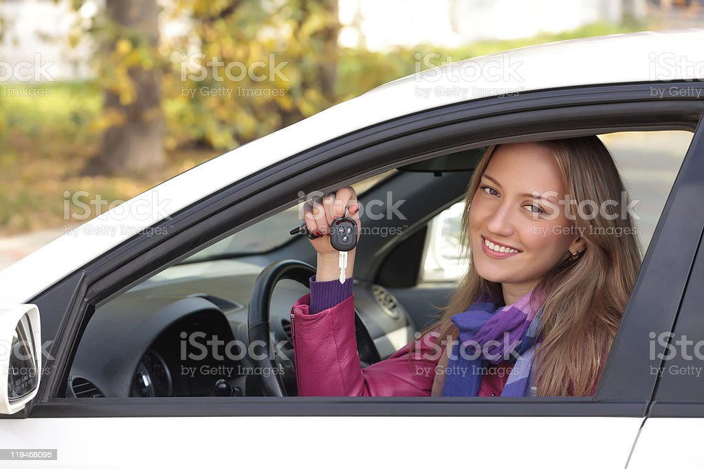 Smiling female sitting in a new car holding up the keys royalty-free stock photo