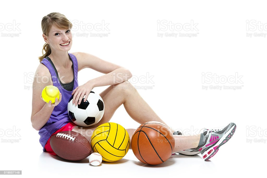 Smiling female sitting with sports ball stock photo