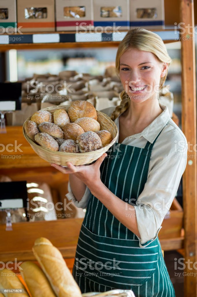 Smiling female staff holding basket of sesame breads at bread counter stock photo