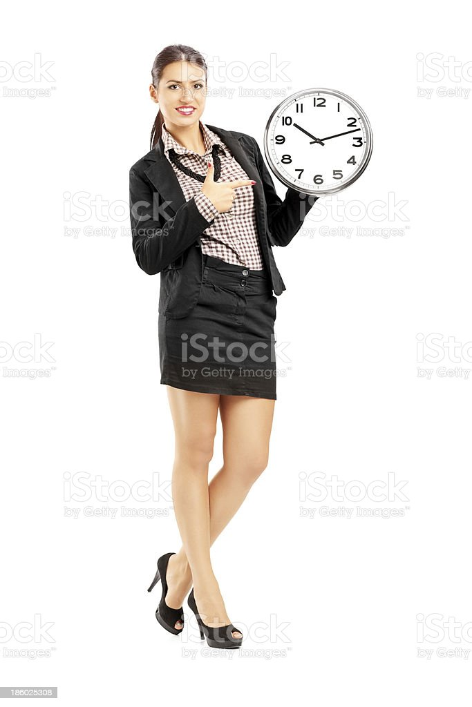 Smiling female standing and pointing on a wall clock royalty-free stock photo