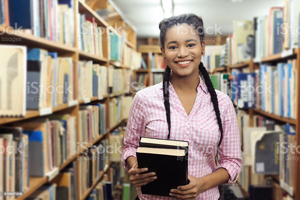 Smiling female student holding books at the library stock photo