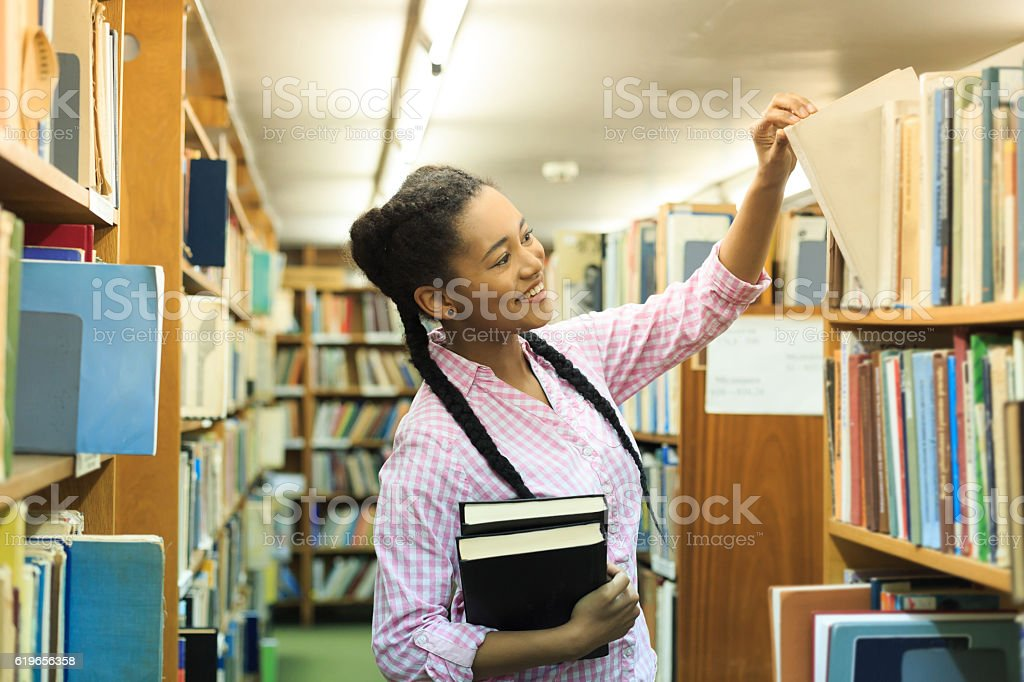 Smiling female student looking for a book at the library stock photo
